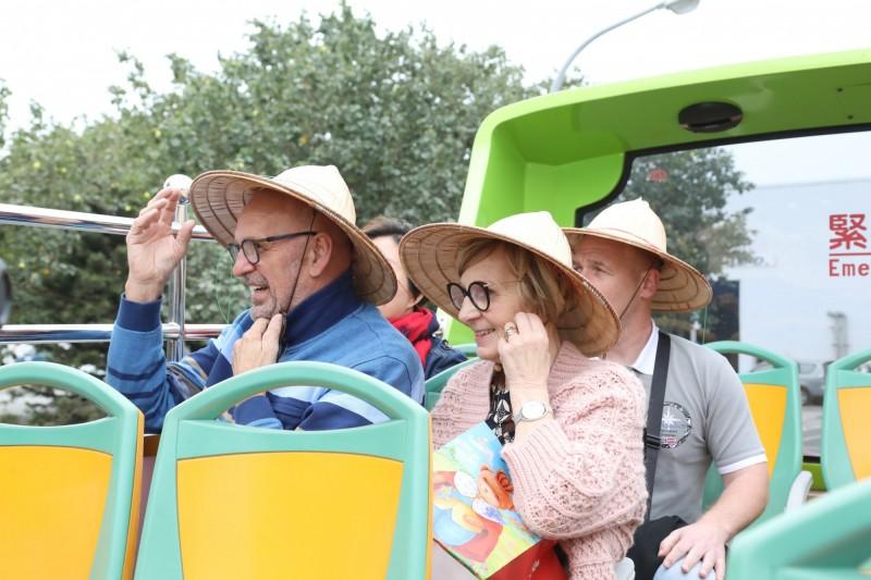 荷蘭美聲音樂家馬丁•賀肯斯(Martin Hurkens)先生賢伉儷,戴斗笠搭雙層巴士遊覽台南風光鮮體驗。(台南市府提供)