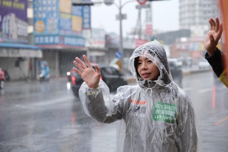 立委洪慈庸不畏低溫下雨站街口,向選民揮手拜票。(洪慈庸服務處提供)