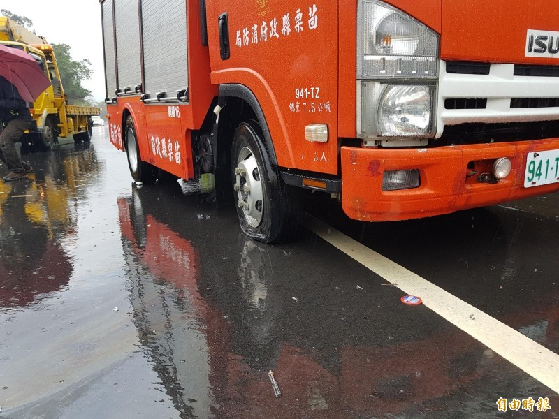 貨車翻覆,消防隊員急於搶救,輪胎壓到鋼片破胎。(記者彭健禮攝)