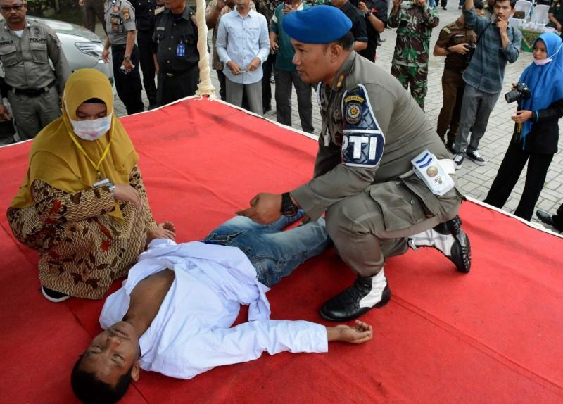 印尼一名男子因發生婚前性行為遭判100下鞭刑,受罰途中被打暈,被現場人員弄醒後把剩下鞭刑打完,才被送到醫院治療。(法新社)