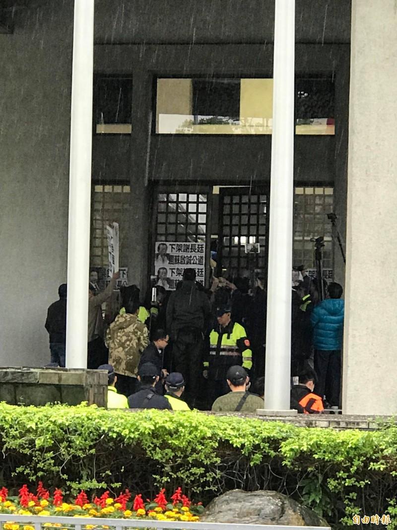 國民黨今率十多人冒雨赴外交部抗議,由於不得其門而入,因此在大門貼上多張「下架謝長廷」海報(記者彭琬馨攝)