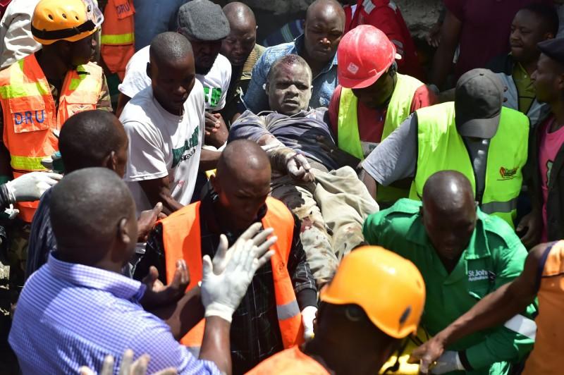 搜救人員協助一名受傷男子脫困,帶離現場。(法新社)