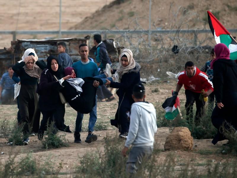 加薩邊境衝突中,巴勒斯坦示威者急忙將受傷的婦人撤離。(法新社)