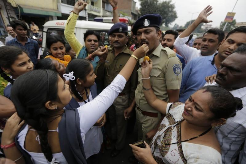 印度婦女向員警餵食糖果,周圍民眾高呼口號,以鼓勵警察殺害4名嫌犯。(美聯社)