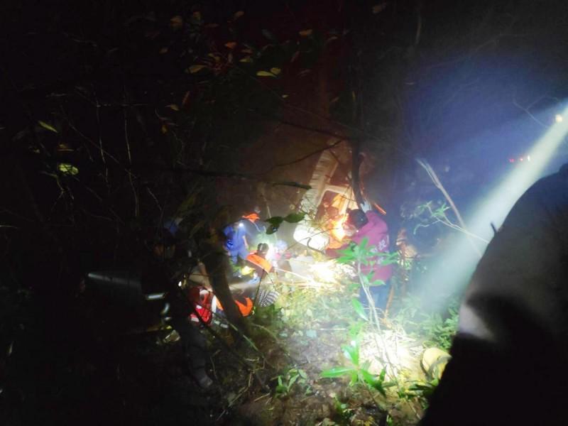 南投縣消防人員正在山谷展開搜救,準備把受困者拉出。(南投縣消防局提供)