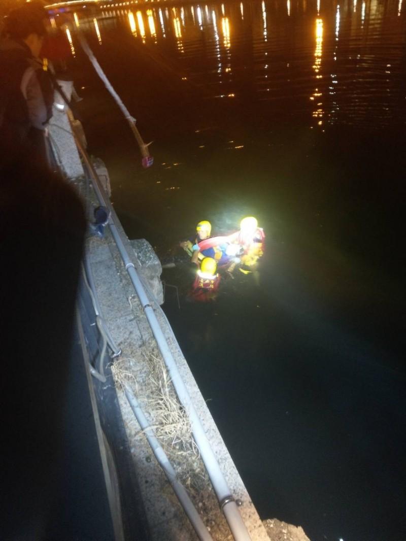 消防人員在冰冷運河裡救起落水的郭姓婦人。(記者王俊忠翻攝)