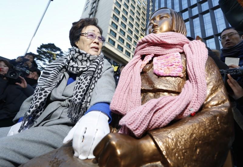 1938年日本駐華領事館與外務省聯絡的機密文件曝光,顯示當時日本陸軍考慮「每70名兵員需要1名左右女招待」。圖為首爾慰安婦銅像(右)與現年92歲的韓國慰安婦老奶奶(左)。(歐新社)