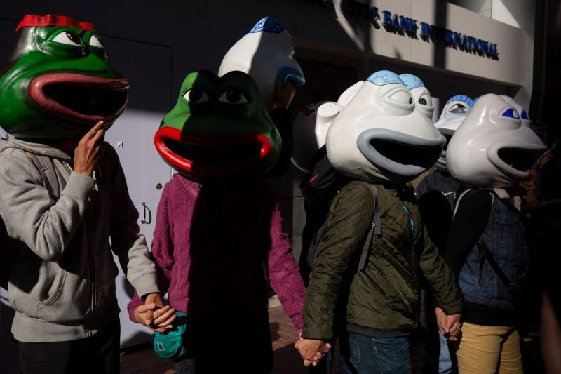 現場有民眾戴著佩佩蛙的頭套,吸引許多人駐足拍照。(法新社)