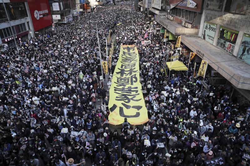 香港大批民眾今(8日)參與「國際人權日遊行」,成千上萬的示威者塞爆大街。(美聯社)