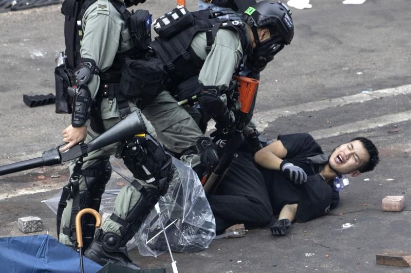 香港反送中運動從6月至今已有200多名年輕人示威者逃往台灣,因為他們擔心被港警拘留時遭到性侵或酷刑。圖為港警壓制示威人士。(美聯社)
