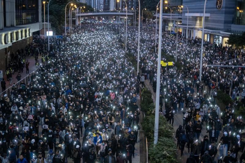 香港民陣舉辦「國際人權日」遊行,入夜後遊行民眾高舉手機,再現「燈海」盛況。(彭博)