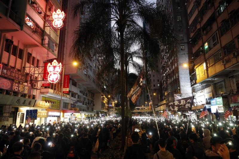 入夜後尚未抵達終點的民眾打開手機手電筒,再現「燈海」。(美聯社)