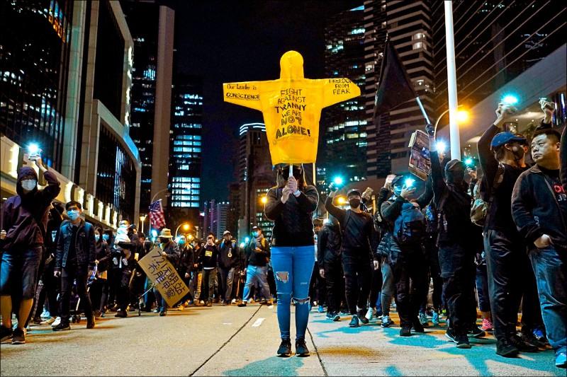一名示威者高舉寫有「對抗專制政權,我們不孤單」字樣的雨衣,表達對港府和北京當局的不滿。(美聯社)