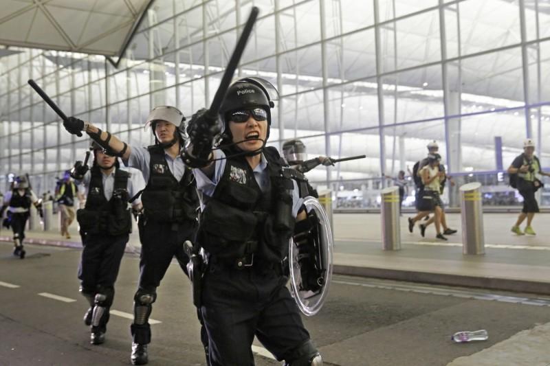 香港警方今(9)日證實,一名休假員警出境旅遊時,因「一時大意」攜帶伸縮警棍至機場。圖為港警持棍示意圖,非當事人。(美聯社)