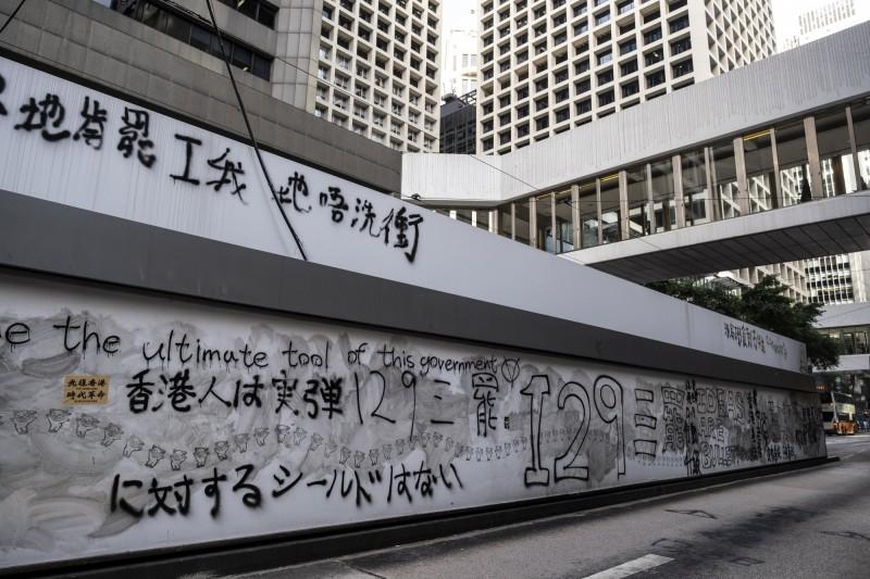 香港今(9)日大三罷,但氣氛較前幾次平靜,不過仍有12人被捕,其中包括7名老師、學生,警方稱「情況令人擔憂」。圖為示威者在牆上寫標語宣傳罷工,上方寫「你們肯罷工,我們不用衝」。(彭博)