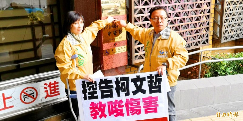 Former Taiwan Solidarity Union legislator Chou Ni-an, left, yesterday rings the bell at the Taipei District Prosecutors' Office before filing a lawsuit against Taipei Mayor Ko Wen-je.   Photo: Huang Chieh, Taipei Times