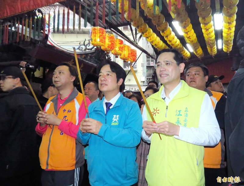 Democratic Progressive Party (DPP) vice presidential candidate William Lai, front center, and DPP Legislator Chiang Yung-chang, front right, offer incense at a temple in New Taipei City's Yonghe District yesterday.  Photo: Chen Hsin-yu, Taipei Times