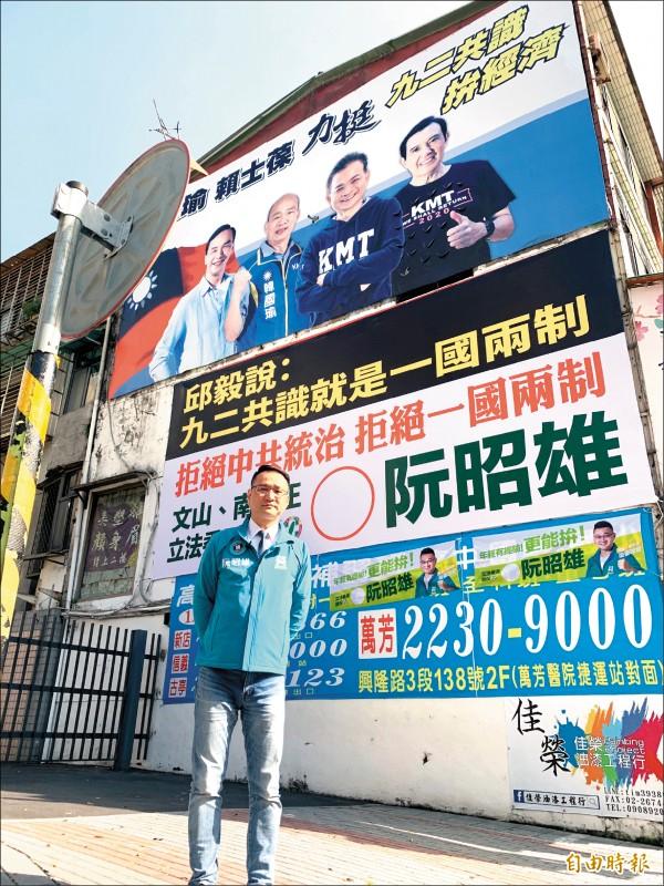 阮昭雄在賴士葆看板下方掛上「九二共識就是一國兩制」看板。 (記者郭安家攝)