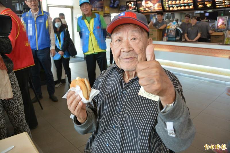 花蓮百歲人瑞王爺爺,因曾說「想吃外國饅頭」,今受邀到連鎖速食店擔任「一日店長」,並獨自享用漢堡圓夢,津津有味,頻頻大讚「真香!」 (記者王峻祺攝)