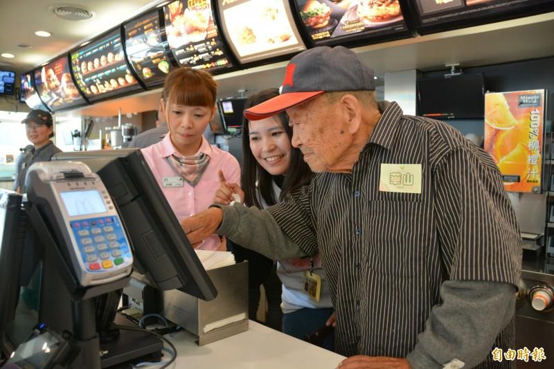 百歲王爺爺在店員指導下為客人點餐,當首次碰觸到點餐機時,還驚喜瞪大雙眼、接連發出讚嘆聲「哇」,臉上掛滿笑容。 (記者王峻祺攝)
