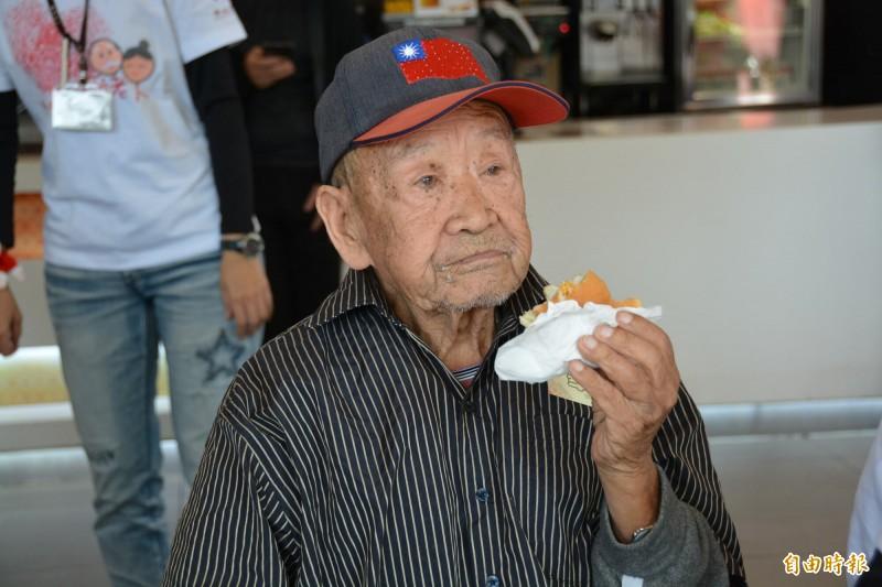 「沒吃過外國饅頭」的花蓮百歲人瑞王爺爺,今受邀享用漢堡,吃得津津有味。(記者王峻祺攝)