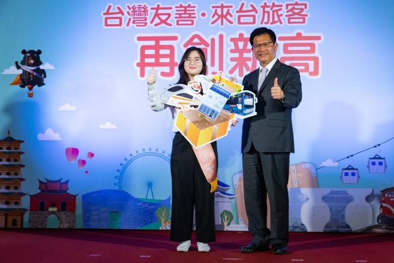 交通部長林佳龍(右)致贈代表機票、住宿、交通票券的好禮包給鄭小姐。(觀光局提供)