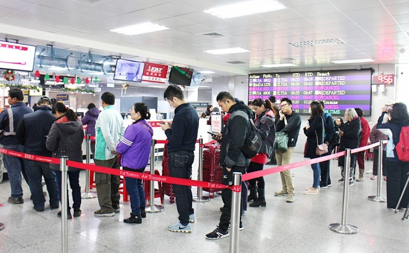 People line up at a Far Eastern Air Transport counter at Kinmen Shangyi Airport yesterday after the airline announced refunds for canceled flights.  Photo: CNA