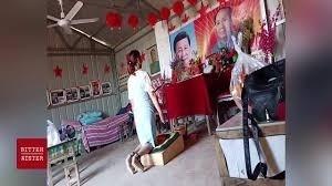 「中原一點紅」廟內,一女子對著習近平和毛澤東畫像跪拜。(影片擷圖)
