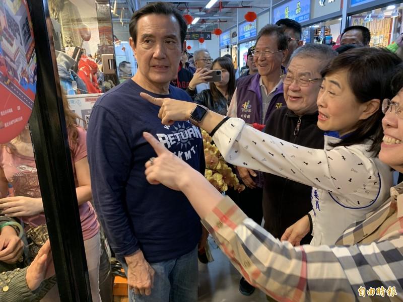 馬英九(左)到南門中繼市場掃街,不少婆婆媽媽開心要合照,林奕華(圖右二)及支持者提醒馬英九「鏡頭在左邊」。(記者郭安家攝)