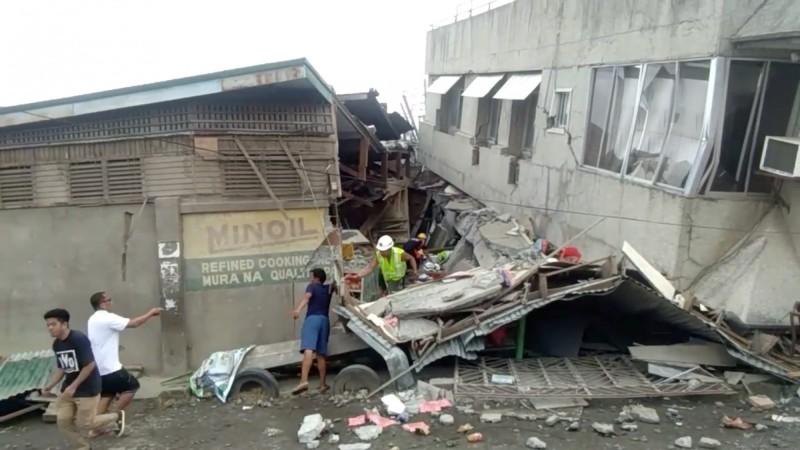 菲律賓民答那峨島今(15)日下午發生規模6.8地震,造成多棟建築倒塌。圖為搜救人員正在帕達達(Padada)1家倒塌的超市搜尋受困人員。(路透)
