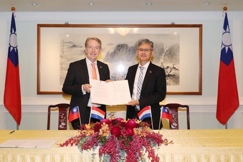 荷蘭貿易暨投資辦事處代表紀維德(左)今天在外交部主秘李光章(右)的見證下完成台荷度假打工備忘錄異地簽署。(外交部提供)