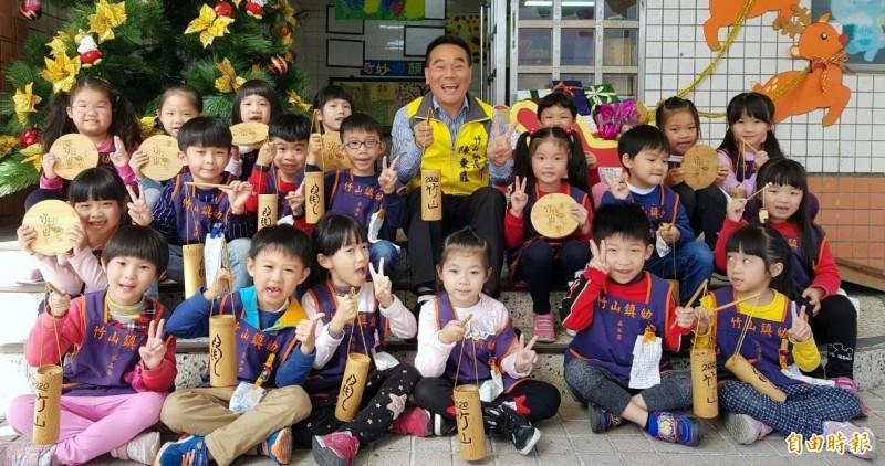 南投縣竹山鎮長陳東睦與小朋友提著竹燈籠,一起行銷「巧巧鼠」竹藝燈會活動。(記者謝介裕攝)