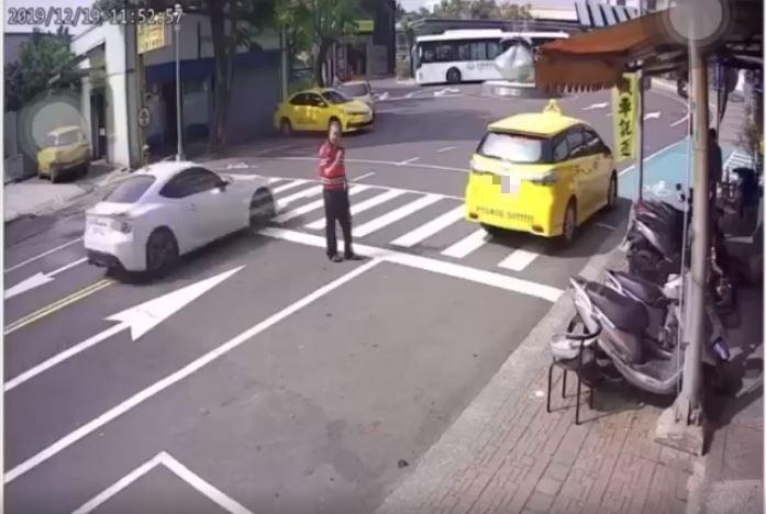 白色小客車從紅衣男子後方呼嘯而過。(圖擷自爆料公社臉書)
