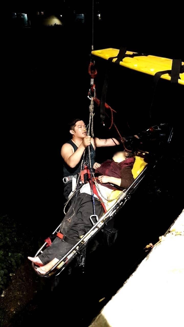 消防隊員吊掛救出墜橋老婦。(記者吳昇儒翻攝)