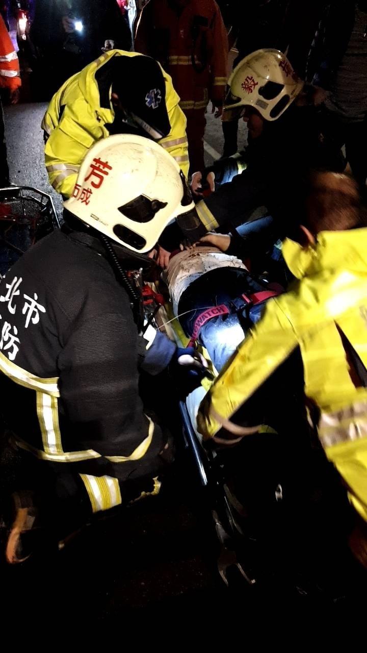 救難人員救起老婦,送醫救治。(記者吳昇儒翻攝)