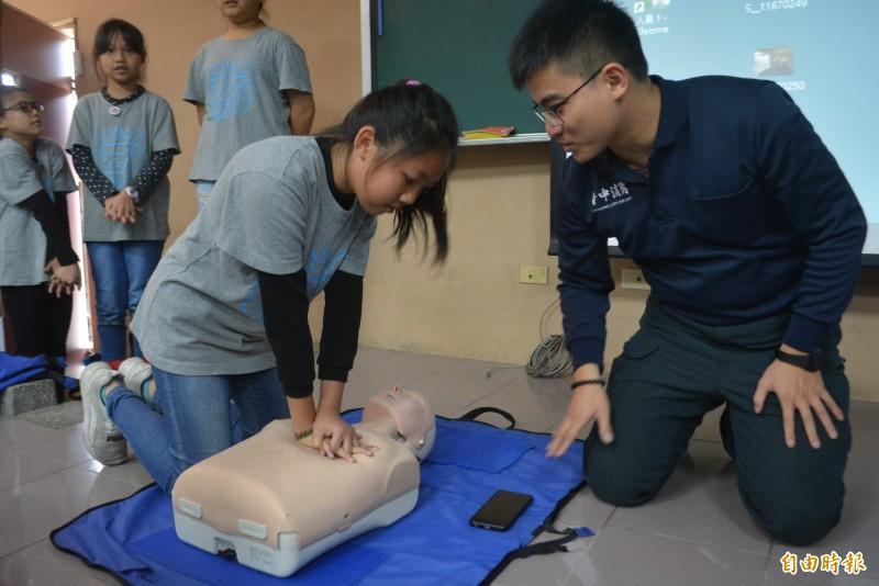 太平光隆國小小朋友,在消防局三大隊教官指導下,學習CPR操作技能。(記者陳建志攝)