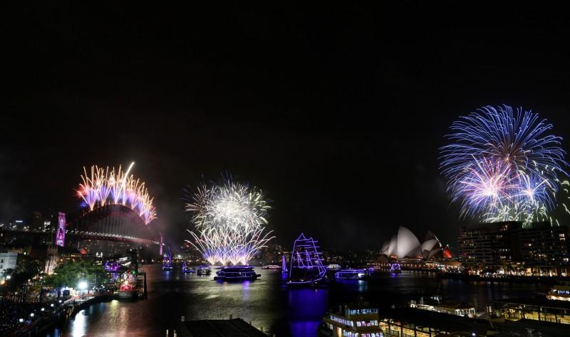 澳洲跨入新年,數十萬人在雪梨歌劇院與港灣大橋附近觀看超過10萬發跨年煙火秀。(歐新社)