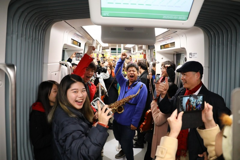 真理大學快閃表演的師生與淡海輕軌乘客同歡倒數,迎接2020新年。(新北捷運公司提供)