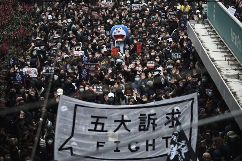 香港民陣今日下午發起元旦大遊行,許多港人上街續爭五大訴求。(法新社)