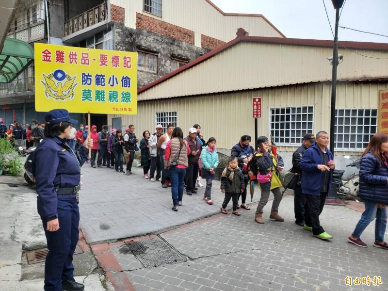 竹山警方持告示牌提醒排隊等待領取錢母的民眾小心小偷。(記者謝介裕攝)