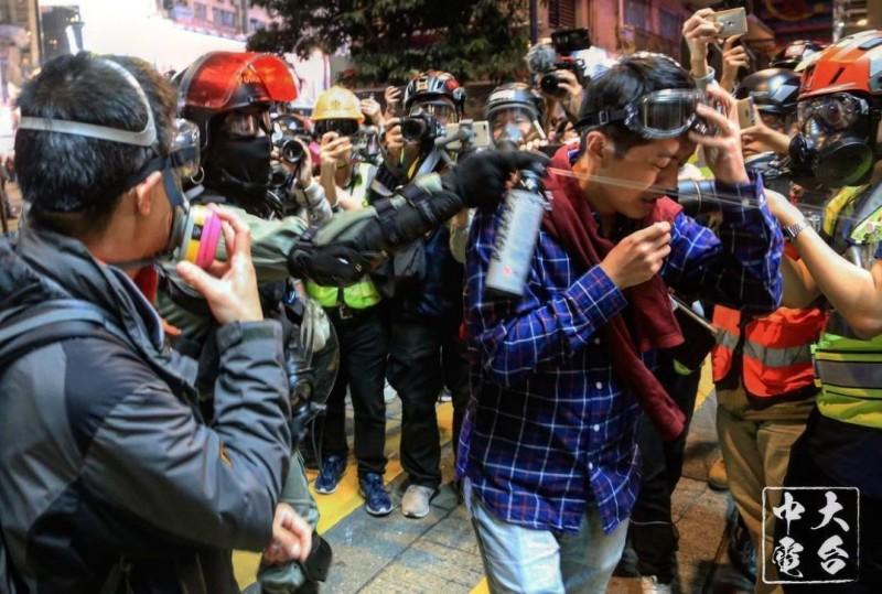 香港立法會區議員許智峯1日晚間在調停警民衝突過程中,遭警方猛然扯下其護目罩、再直朝其臉部噴射胡椒噴霧。(圖擷取自臉書_中大校園電台 CUHK Campus Radio)