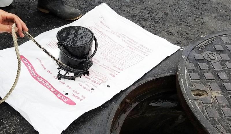 市府發現遭人從污水人孔傾倒有機油泥。(記者陳文嬋翻攝)