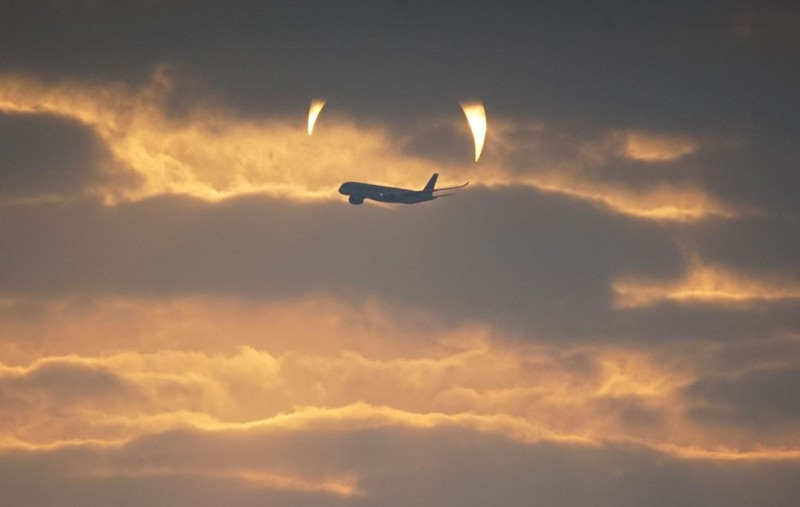 太陽升到中空後,因日食呈現倒月牙形,還正巧有一架飛機經過,看起來就像一對「金色惡魔獠牙」準備攻擊飛機。(圖獲攝影師 Elias Chasiotis 授權)