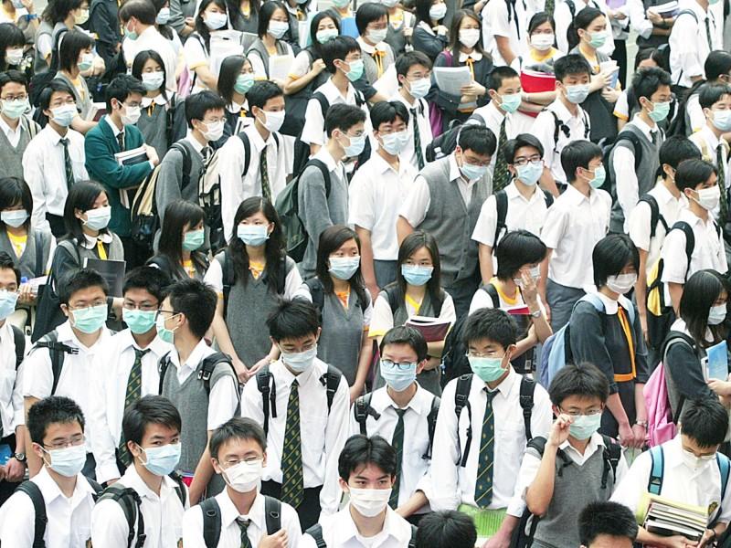 世界衛生組織(WHO)8日表示,根據初步資訊研判,武漢不明肺炎可能為類似SARS、MERS的新型病毒引起。圖為2003年香港爆發SARS疫情,民眾戴口罩防疫。(路透資料照)