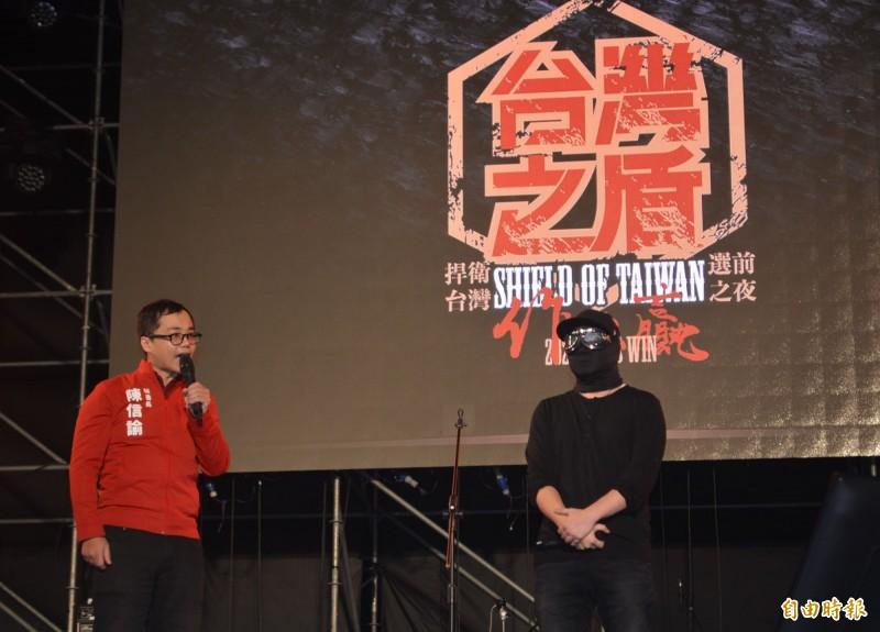 一名香港勇武派記者(右)今晚蒙面現身台灣基進「台灣之盾」晚會,呼籲大家明天踴躍投票。(記者陳建志攝)