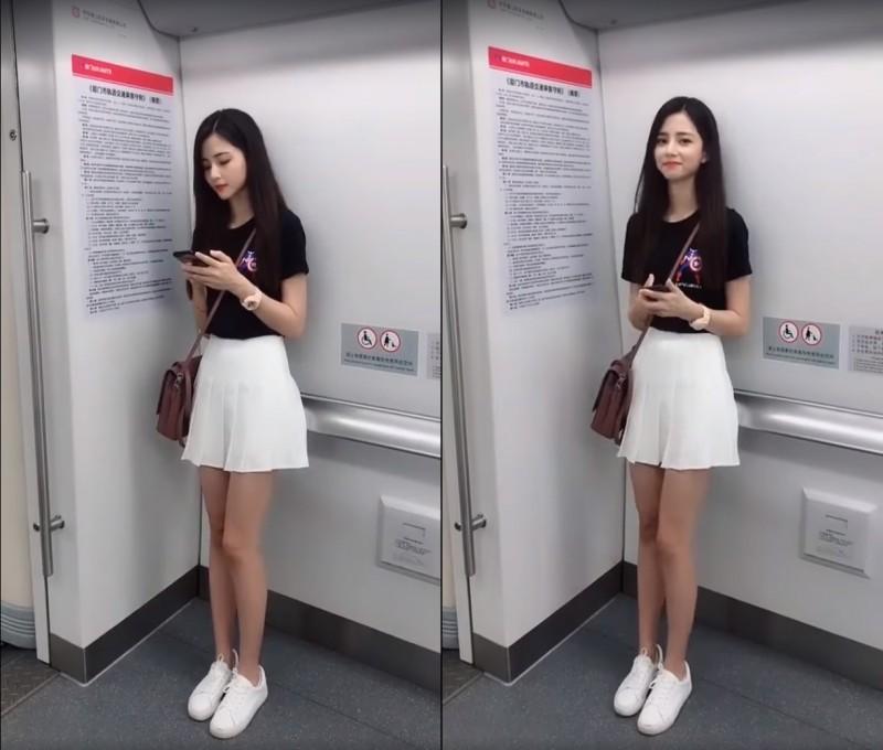 正妹穿著黑色上衣,下身一件白色百褶短裙,露出一雙修長纖細的美腿,隨著列車行進在車廂中前後晃動,還可愛地不小心撞到牆壁。最後,她還向鏡頭甜甜一笑放電。(擷取自「JKF 紅燈區2.0」臉書影片)