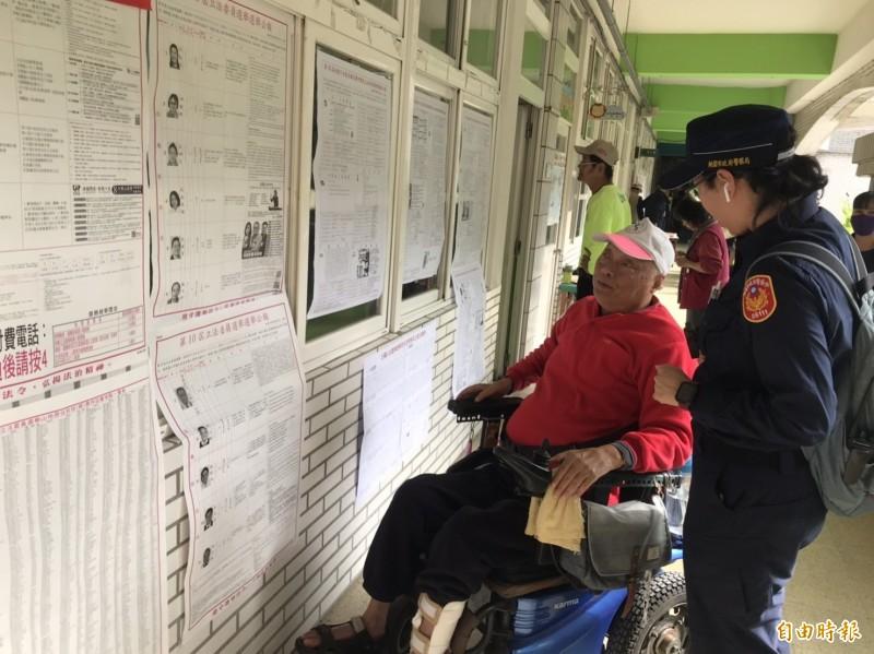 警員細心提醒長者投票注意事項。(記者許倬勛攝)