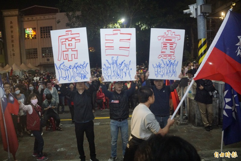 韓粉群聚總部大門口,高舉牌誌呼喊「支持韓國瑜選黨主席」。(記者黃佳琳攝)