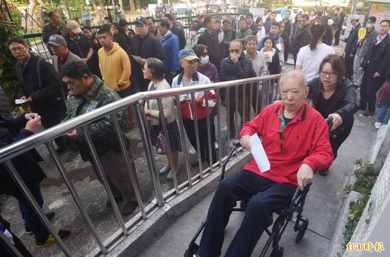 總統、立委選舉11日舉行,一早投票所外民眾大排長龍投票,行動不便的長者由家屬推著輪椅前來投票。(記者廖振輝攝)