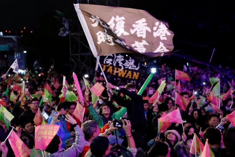 民進黨中央黨部外有香港示威者揮舞「光復香港,時代革命」旗幟,慶賀蔡英文順利連任總統。(路透)